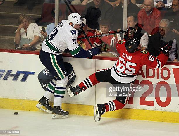Andrew Shaw of the Chicago Blackhawks is checked into the boards by Alexander Edler of the Vancouver Canucks at the United Center on March 21 2012 in...