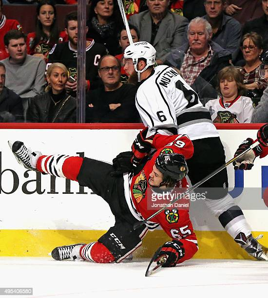 Andrew Shaw of the Chicago Blackhawks is dumped to the ice by Jake Muzzin of the Los Angeles Kings at the United Center on November 2 2015 in Chicago...