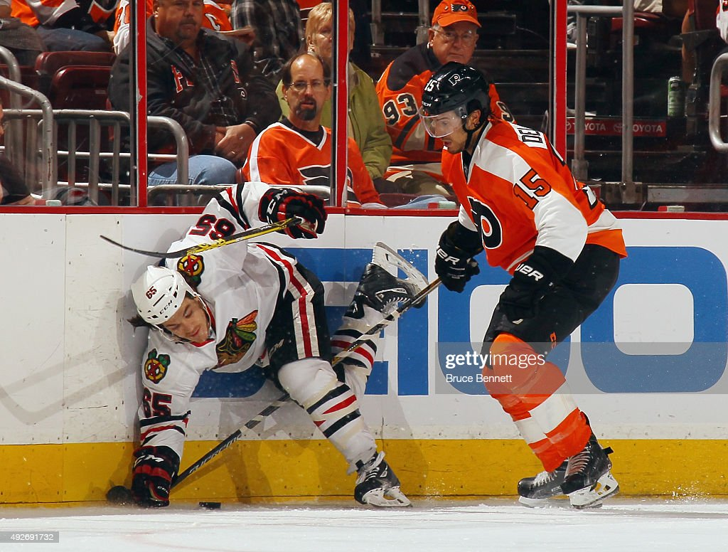 Andrew Shaw #65 of the Chicago Blackhawks is hit into the boards by Michael Del Zotto #15 of the Philadelphia Flyers during the second period at the Wells Fargo Center on October 14, 2015 in Philadelphia, Pennsylvania.