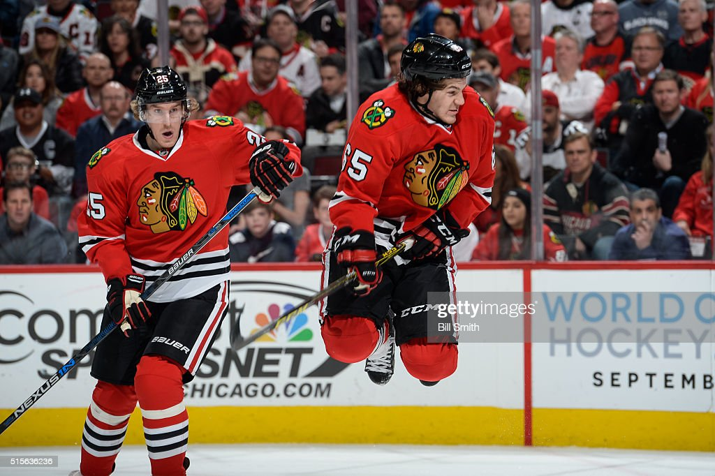 Andrew Shaw #65 of the Chicago Blackhawks jumps out of the way of the puck as teammate Dale Weise #25 watches behind in the first period of the NHL game against the Los Angeles Kings at the United Center on March 14, 2016 in Chicago, Illinois.
