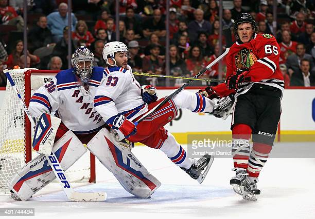 Andrew Shaw of the Chicago Blackhawks knocks Keith Yandle of the New York Rangers to the ice in front of Henrik Lindqvist at the United Center on...