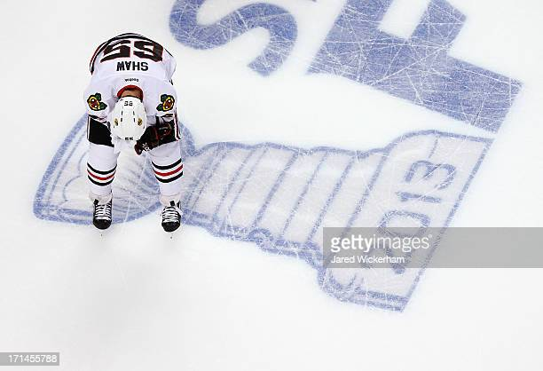 Andrew Shaw of the Chicago Blackhawks skates off of the ice holding a towel to his bloody face following a play in the first period against the...