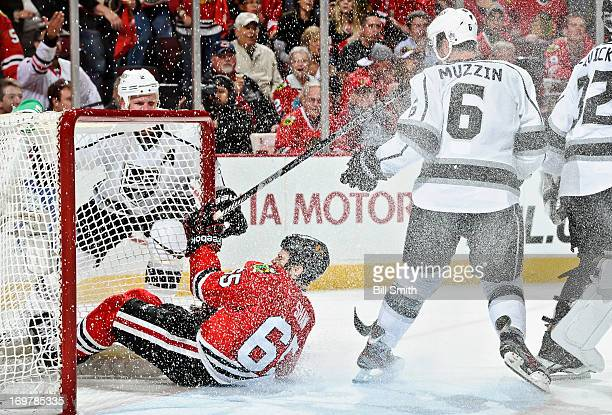 Andrew Shaw of the Chicago Blackhawks slides into the goal past Jake Muzzin of the Los Angeles Kings as Matt Greene of the Kings watches from behind...