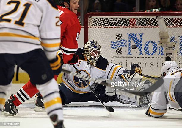 Andrew Shaw of the Chicago Blackhawks slips the puck past Jhonas Enroth of the Buffalo Sabres for a goal at the United Center on January 18 2012 in...
