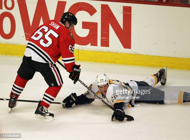 Andrew Shaw of the Chicago Blackhawks tries to knock the puck out of the reach of Ryan Suter of the Nashville Predators at the United Center on March...
