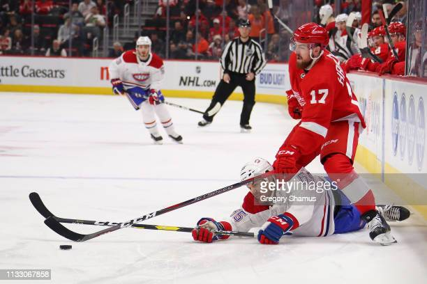 Andrew Shaw of the Montreal Canadiens battles for the puck with Filip Hronek of the Detroit Red Wings during the first period at Little Caesars Arena...