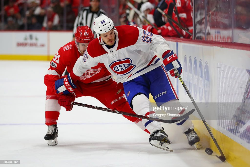 Andrew Shaw #65 of the Montreal Canadiens battles to control the puck in front of Xavier Ouellet #61 of the Detroit Red Wings during the third period at Little Caesars Arena on November 30, 2017 in Detroit, Michigan. Montreal won the game 6-3.