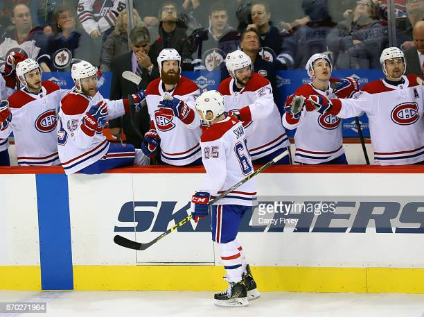 Andrew Shaw of the Montreal Canadiens celebrates his first period goal against the Winnipeg Jets with teammates at the bench at the Bell MTS Place on...