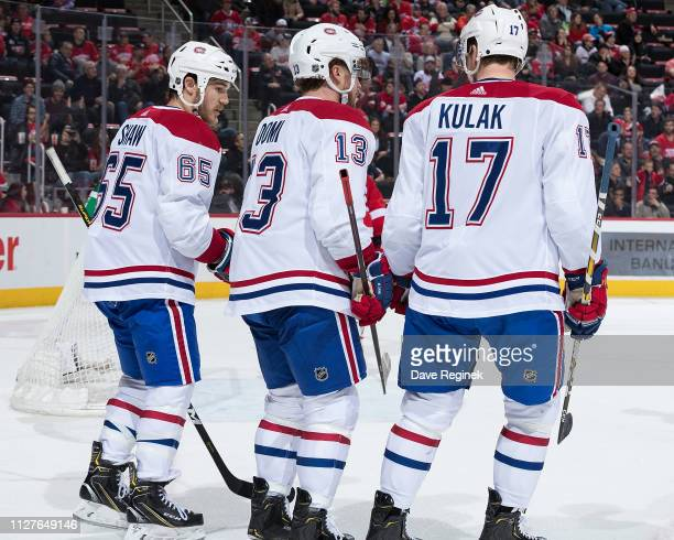 Andrew Shaw of the Montreal Canadiens celebrates his second goal in the second period with teammates Max Domi and Brett Kulak during an NHL game...