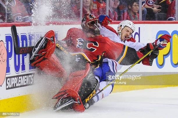 Andrew Shaw of the Montreal Canadiens collides with Mike Smith of the Calgary Flames during an NHL game at Scotiabank Saddledome on December 22 2017...
