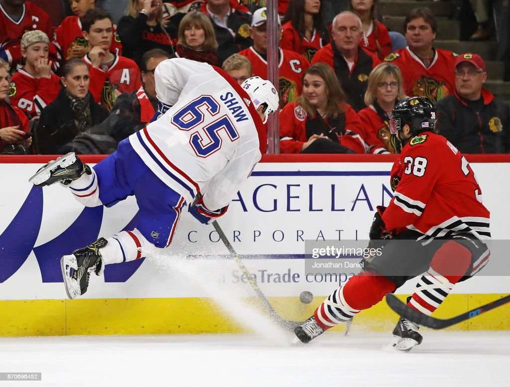 Andrew Shaw #65 of the Montreal Canadiens leaps in the air to take the puck away from Ryan Hartman #38 of the Chicago Blackhawks at the United Center on November 5, 2017 in Chicago, Illinois. The Canadiens defeated the Blackhawks 2-0.