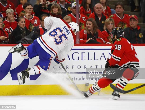Andrew Shaw of the Montreal Canadiens leaps in the air to take the puck away from Ryan Hartman of the Chicago Blackhawks at the United Center on...