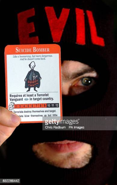Andrew Sheering one of the designers behind 'War On Terror The Board Game' wears a balaclava from the game and holds a 'suicide bomber' playing card...