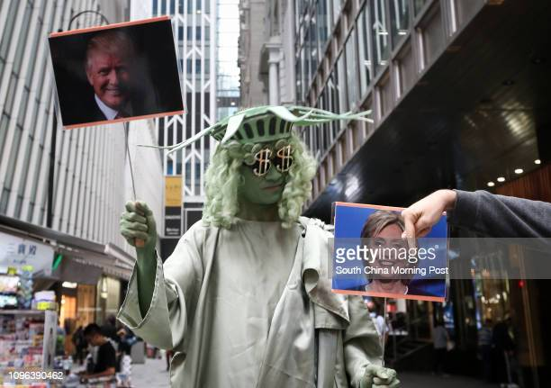 Andrew So director of HK Funny Clown Theatre dressed as Statue of Liberty holding photos of Donald Trump and Hillary Clinton in Central 09NOV16...