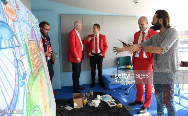 Andrew Strauss and Eoin Morgan with artist Sacha Jafri who is painting a piece to be auctioned off to raise funds for Ruth Strauss Foundation during...