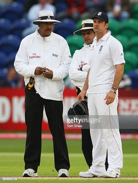 Andrew Strauss of England looks to the sky with umpires Billy Doctrove and Aleem Dar after play was suspended during day three of the npower 1st...