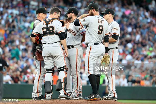 Andrew Suarez of the San Francisco Giants and teammates discuss play after loading the bases without any outs in the fourth inning against the...