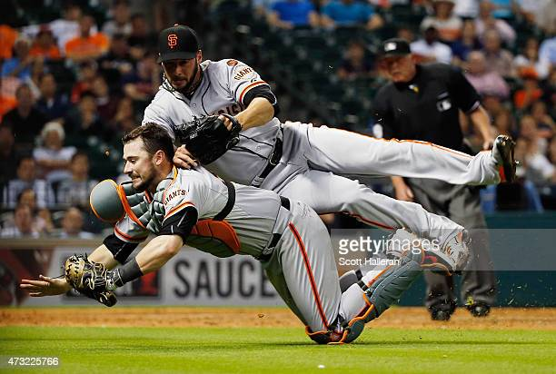 Andrew Susac of the San Francisco Giants makes a play on a foul ball as his pitcher George Kontos tumbles over him in the seventh inning of their...