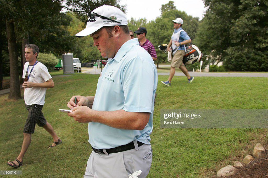 Andrew Svoboda writes in his scorecard while walking from the 17th green to the 18th tee during the final round of the Chiquita Classic in the Web.com tour finals at River Run Country Club on September 8, 2013 in Davidson, North Carolina.