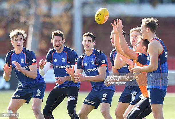 Andrew Swallow Ben Cunnington Jack Ziebell and their Kangaroos teammates practise catching the ball during a North Melbourne Kangaroos AFL training...