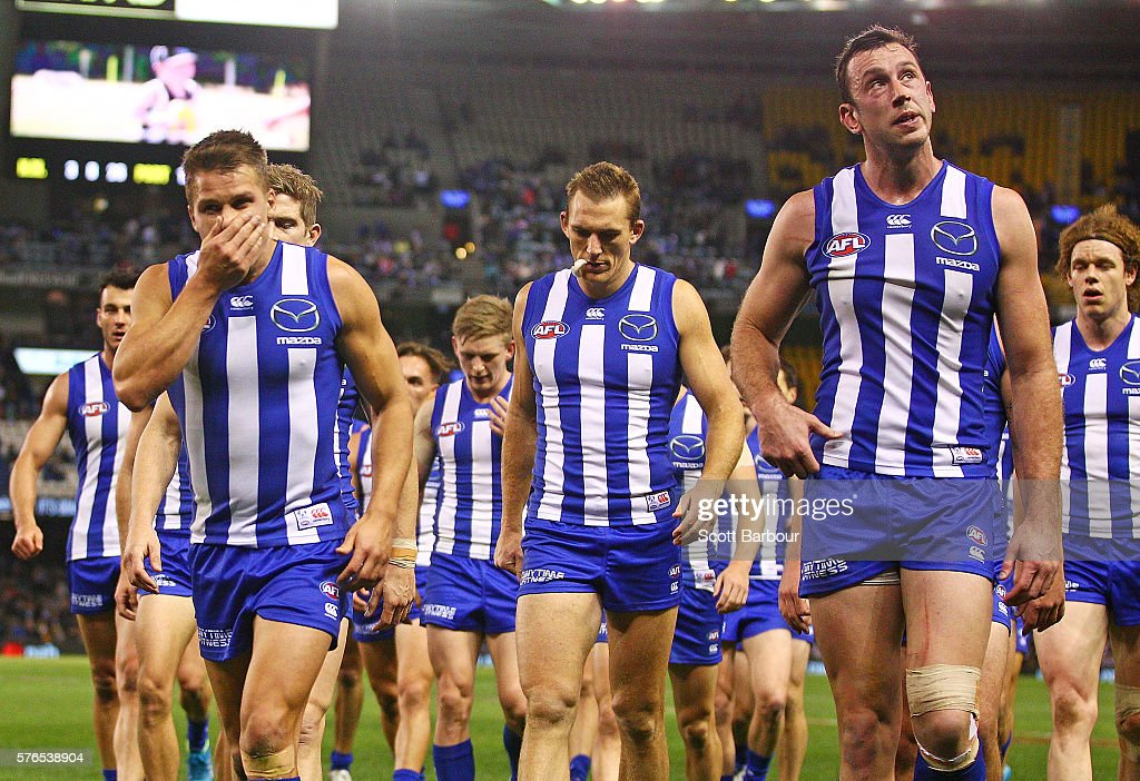 Andrew Swallow, Drew Petrie, Todd Goldstein and Ben Brown of the Kangaroos look dejected as they leave the field during the round 17 AFL match between the North Melbourne Kangaroos and the Port Adelaide Power at Etihad Stadium on July 16, 2016 in Melbourne, Australia.
