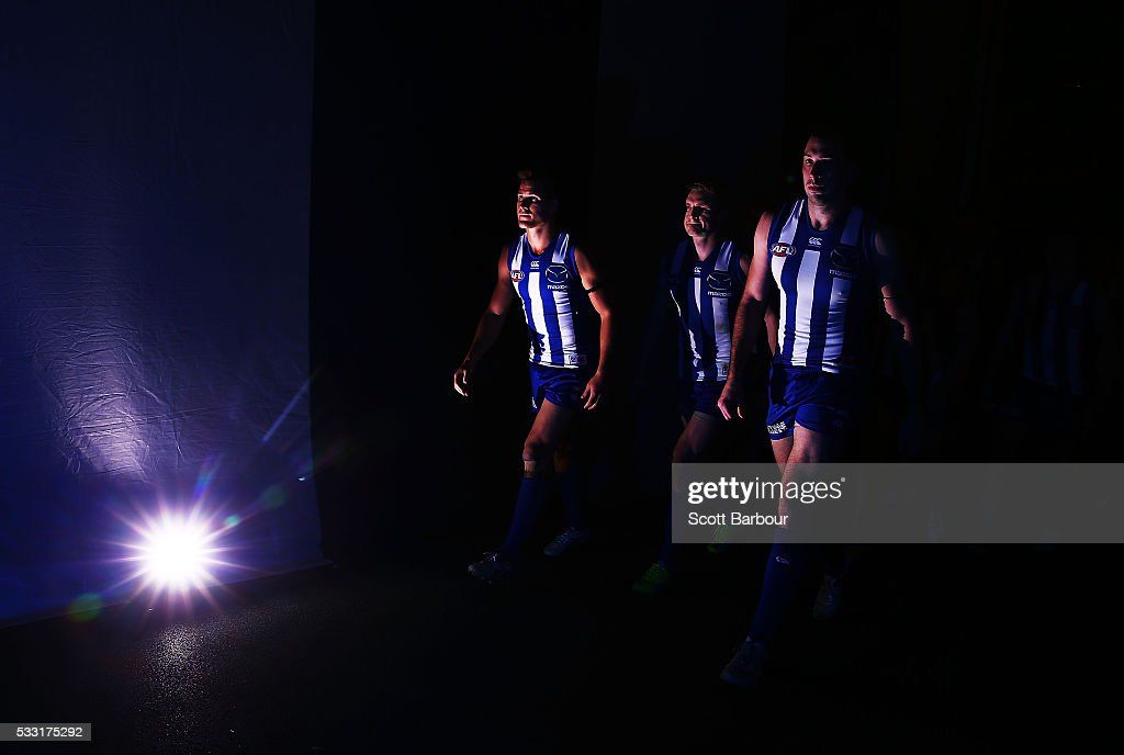 Andrew Swallow , Jack Ziebell and Todd Goldstein of the Kangaroos lead their players onto the field during the round nine AFL match between the North Melbourne Kangaroos and the Carlton Blues at Etihad Stadium on May 21, 2016 in Melbourne, Australia.