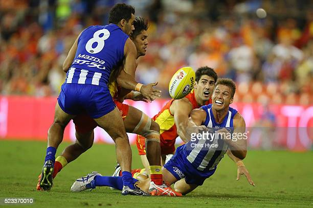Andrew Swallow of the Kangaroos handballs during the round five AFL match between the Gold Coast Suns and the North Melbourne Kangaroos at Metricon...