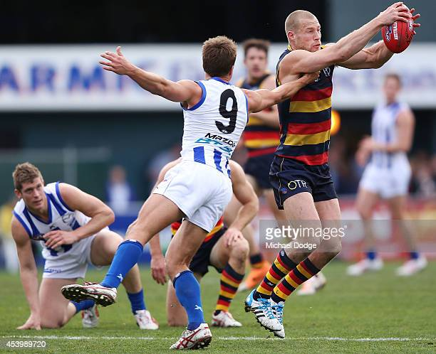 Andrew Swallow of the Kangaroos tackles Scott Thompson of the Crows during the round 22 AFL match between the North Melbourne Kangaroos and the...