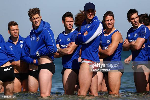 Andrew Swallow walks through water with teammates during a North Melbourne Kangaroos AFL recovery session on September 14 2015 in Melbourne Australia