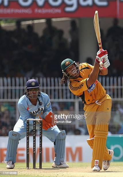 Andrew Symonds of Australia straight drives for six with MS Dhoni of India looking on during the sixth one day international match between India and...