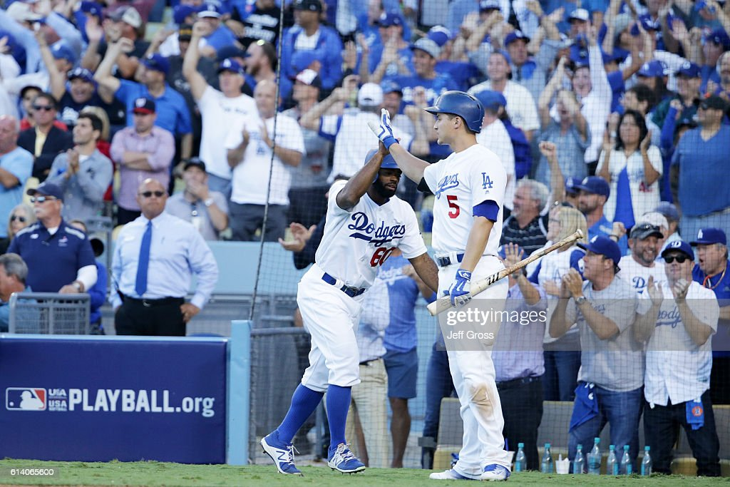 Andrew Toles #60 of the Los Angeles Dodgers celebrates with Corey Seager #5 after scoring on a single by Chase Utley #26 in the eighth inning during game four of the National League Division Series at Dodger Stadium on October 11, 2016 in Los Angeles, California.