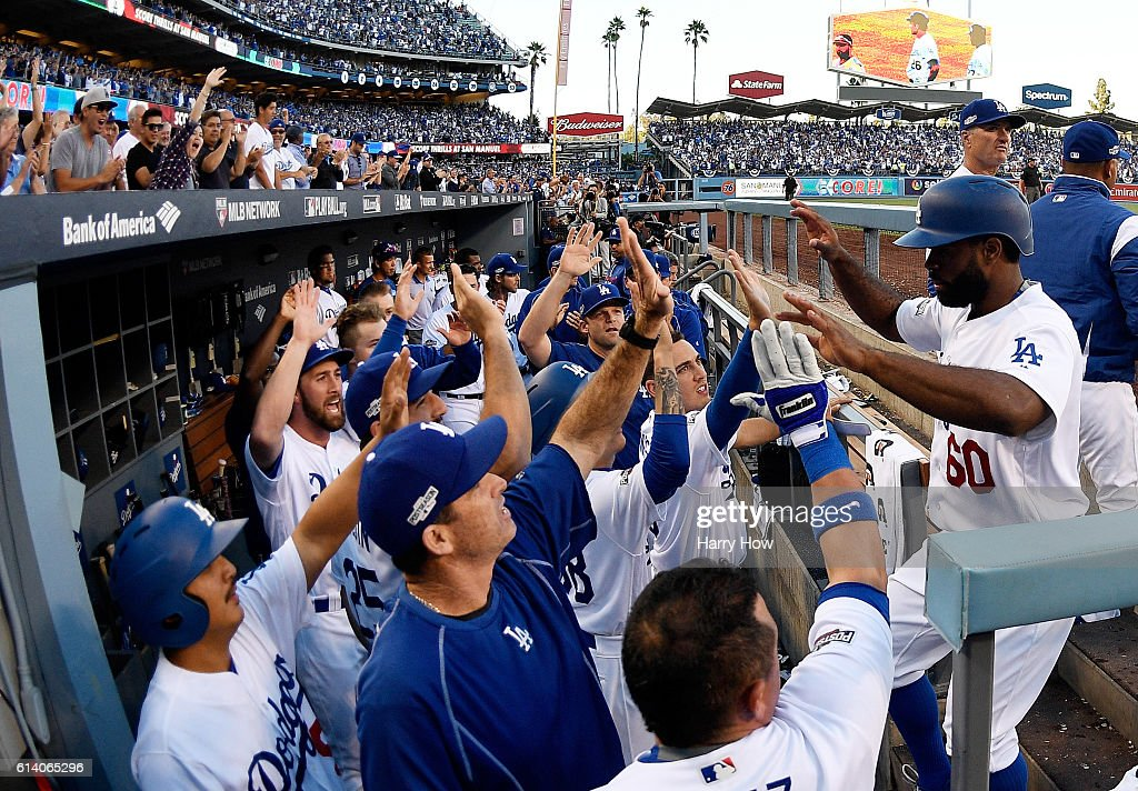 Andrew Toles #60 of the Los Angeles Dodgers celebrates with teammates in the eighth inning after scoring on a single by Chase Utley #26 during game four of the National League Division Series against the Washington Nationals at Dodger Stadium on October 11, 2016 in Los Angeles, California.