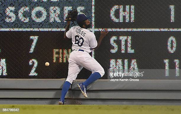 Andrew Toles of the Los Angeles Dodgers crashes into the wall going for a triple by David Peralta of the Arizona Diamondbacks in the ninth inning of...