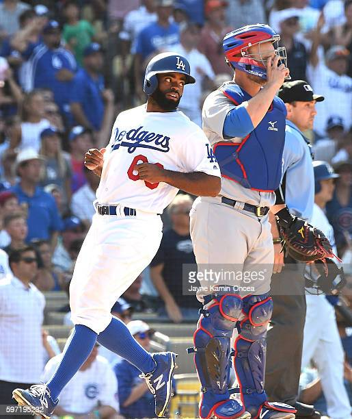 Andrew Toles of the Los Angeles Dodgers crosses the plate in front of David Ross of the Chicago Cubs for the winning run in the ninth inning of the...