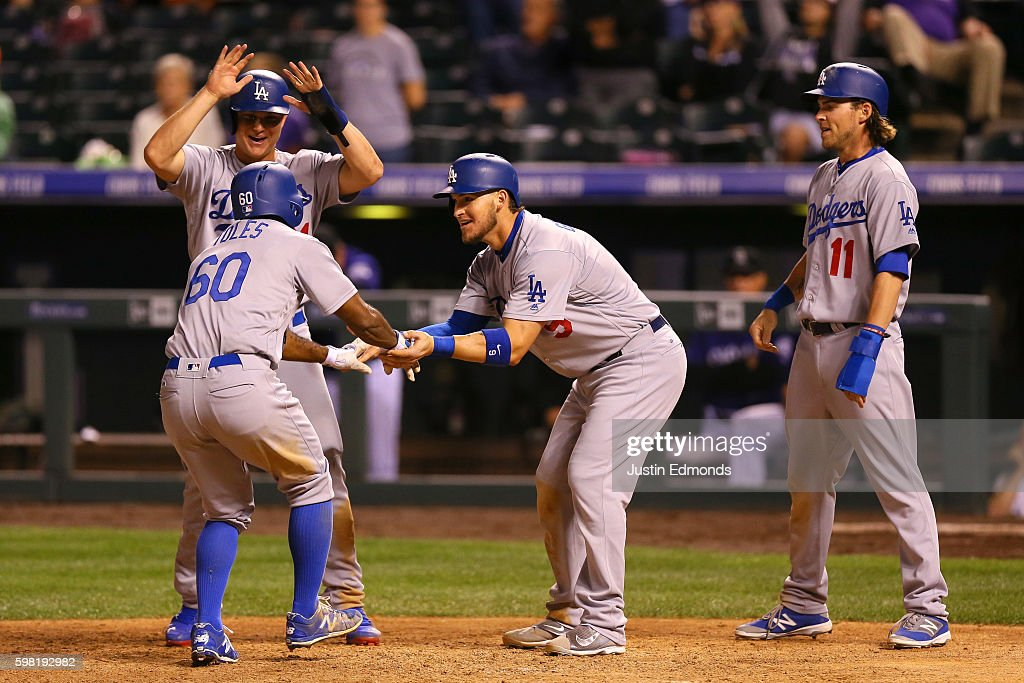 Andrew Toles #60 of the Los Angeles Dodgers is greeted at home plate by Joc Pederson #31, Yasmani Grandal #9 and Josh Reddick #11 after hitting a go-ahead grand slam in the ninth inning against the Colorado Rockies at Coors Field on August 31, 2016 in Denver, Colorado. The Dodgers defeated the Rockies 10-8 to avoid the series sweep.