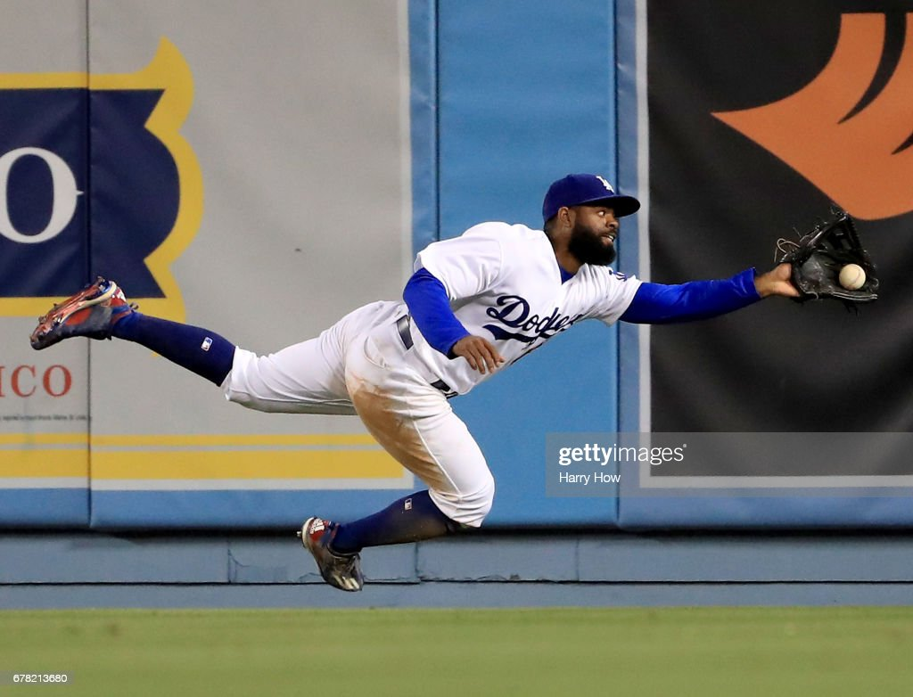 Andrew Toles #60 of the Los Angeles Dodgers makes a running catch for an out of Hunter Pence #8 of the San Francisco Giants during the 11th inning at Dodger Stadium on May 3, 2017 in Los Angeles, California.