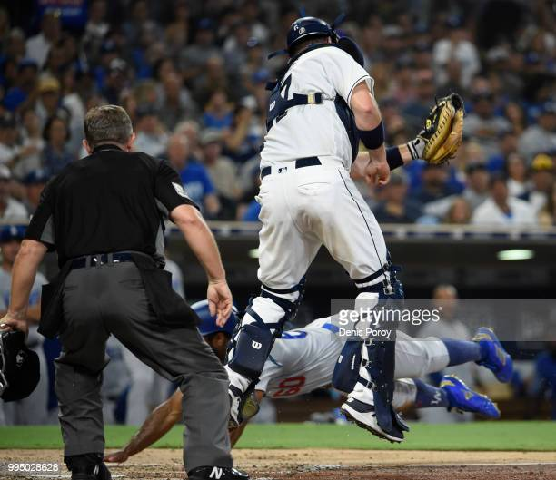 Andrew Toles of the Los Angeles Dodgers scores ahead of the throw to AJ Ellis of the San Diego Padres during the fifth inning of a baseball game at...