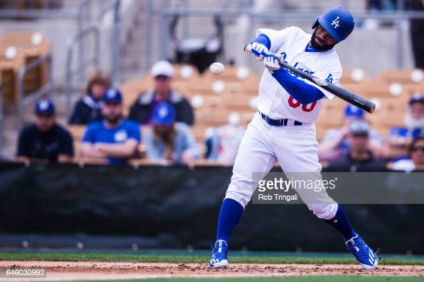 Andrew Toles of the Los Angeles Dodgers singles in the second inning during a spring training game against the Colorado Rockies at Camelback Ranch on...