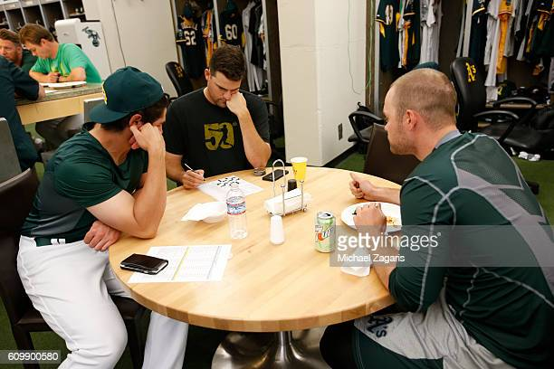 Andrew Triggs and Daniel Coulombe of the Oakland Athletics work on a crossword in the clubhouse prior to the game against the Los Angeles Angels of...
