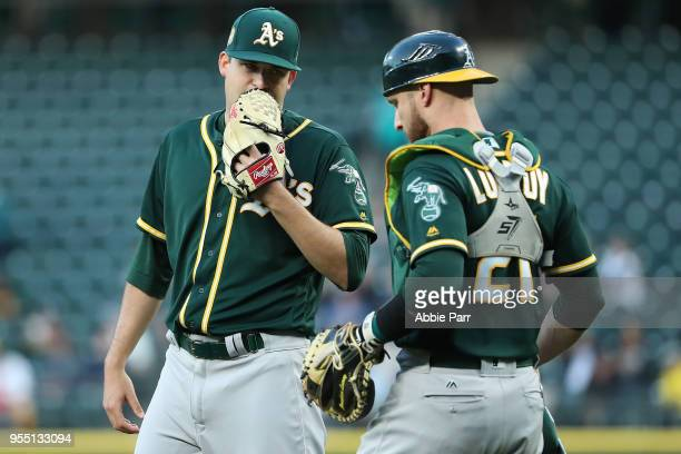Andrew Triggs and Jonathan Lucroy of the Oakland Athletics have a conversation in the third inning against the Seattle Mariners during their game at...