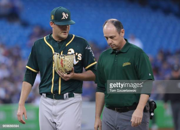Andrew Triggs of the Oakland Athletics exits the game with a forearm strain with the trainer in the third inning during MLB game action against the...