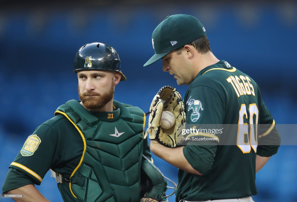 Andrew Triggs #60 of the Oakland Athletics is visited on the mound by Jonathan Lucroy #21 momenst before leaving the game with a forearm strain in the third inning during MLB game action against the Toronto Blue Jays at Rogers Centre on May 17, 2018 in Toronto, Canada.