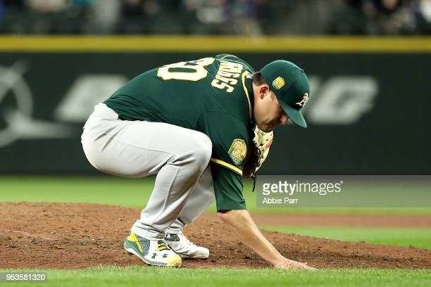 Andrew Triggs of the Oakland Athletics reacts after giving up a three run home run to Nelson Cruz of the Seattle Mariners in the fifth inning to give...