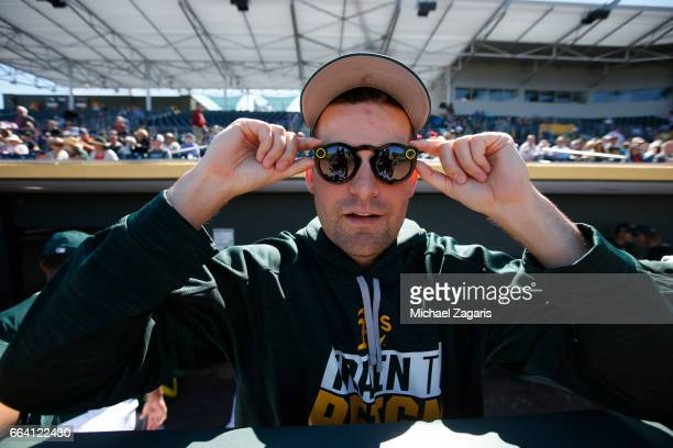 Andrew Triggs of the Oakland Athletics tries out new video glasses in the dugout prior to the game against the Texas Rangers at Hohokam Stadium on...