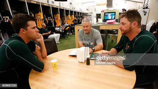 Andrew Triggs Pitching Coach Curt Young and Stephen Vogt of the Oakland Athletics go over batters in the clubhouse prior to the game against the...