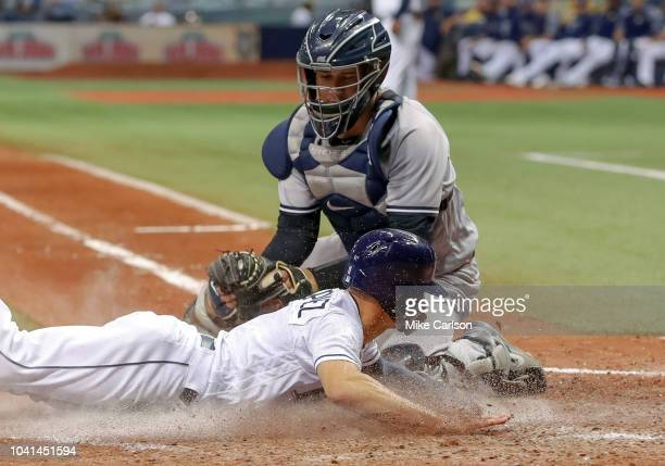 Andrew Velazquez of the Tampa Bay Rays slides in safely ahead of a tag from Gary Sanchez of the New York Yankees on a fielder's choice hit by Willy...