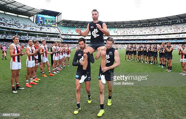 Andrew Walker of the Blues is chaired from the field by Kade Simpson of the Blues and Bryce Gibbs of the Blues as he leaves the field after playing...