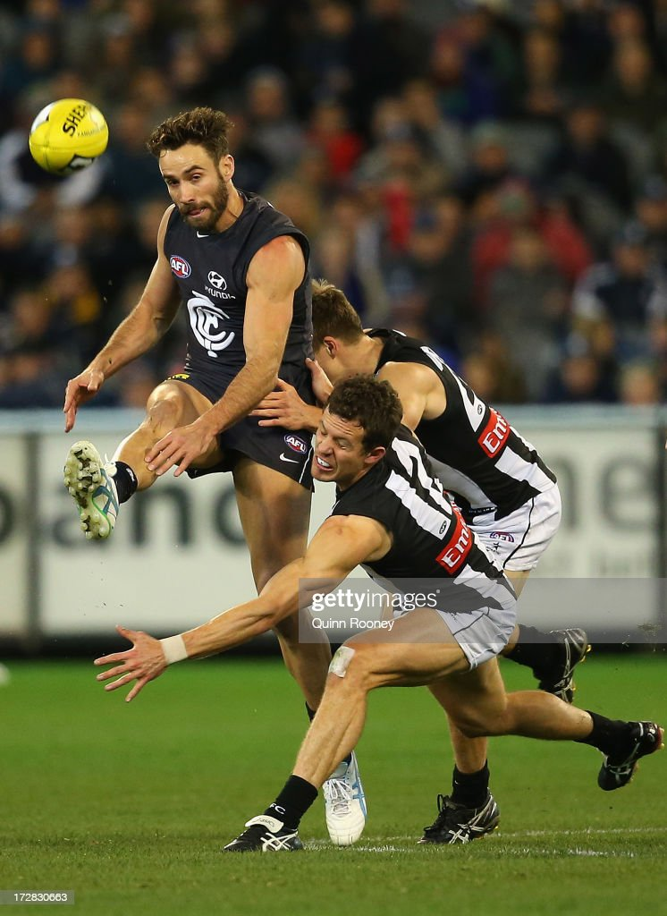 Andrew Walker of the Blues kicks as Luke Ball of the Magpies attempts to smouther during the round 15 AFL match between the Carlton Blues and the Collingwood Magpies at Melbourne Cricket Ground on July 5, 2013 in Melbourne, Australia.