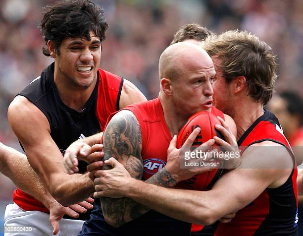 Andrew Welsh and Patrick Ryder of the Bombers tackle Nathan Jones of the Demons during the round 15 AFL match between the Melbourne Demons and the...