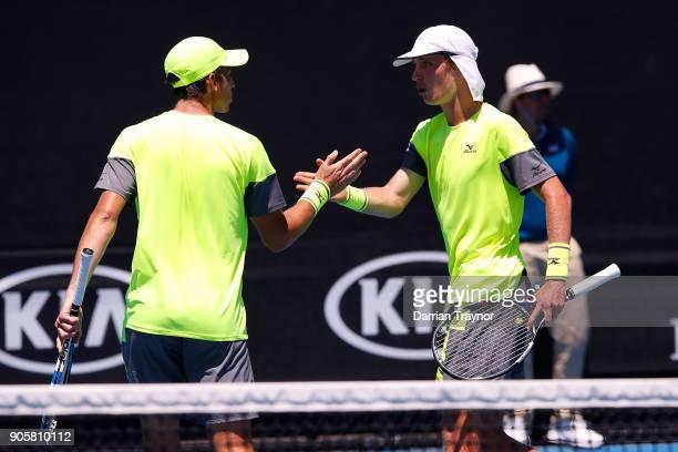 Andrew Whittington of Australia and Marc Polmans of Australia talk tactics in their first round men's doubles match against Juan Sebastian Cabal of...